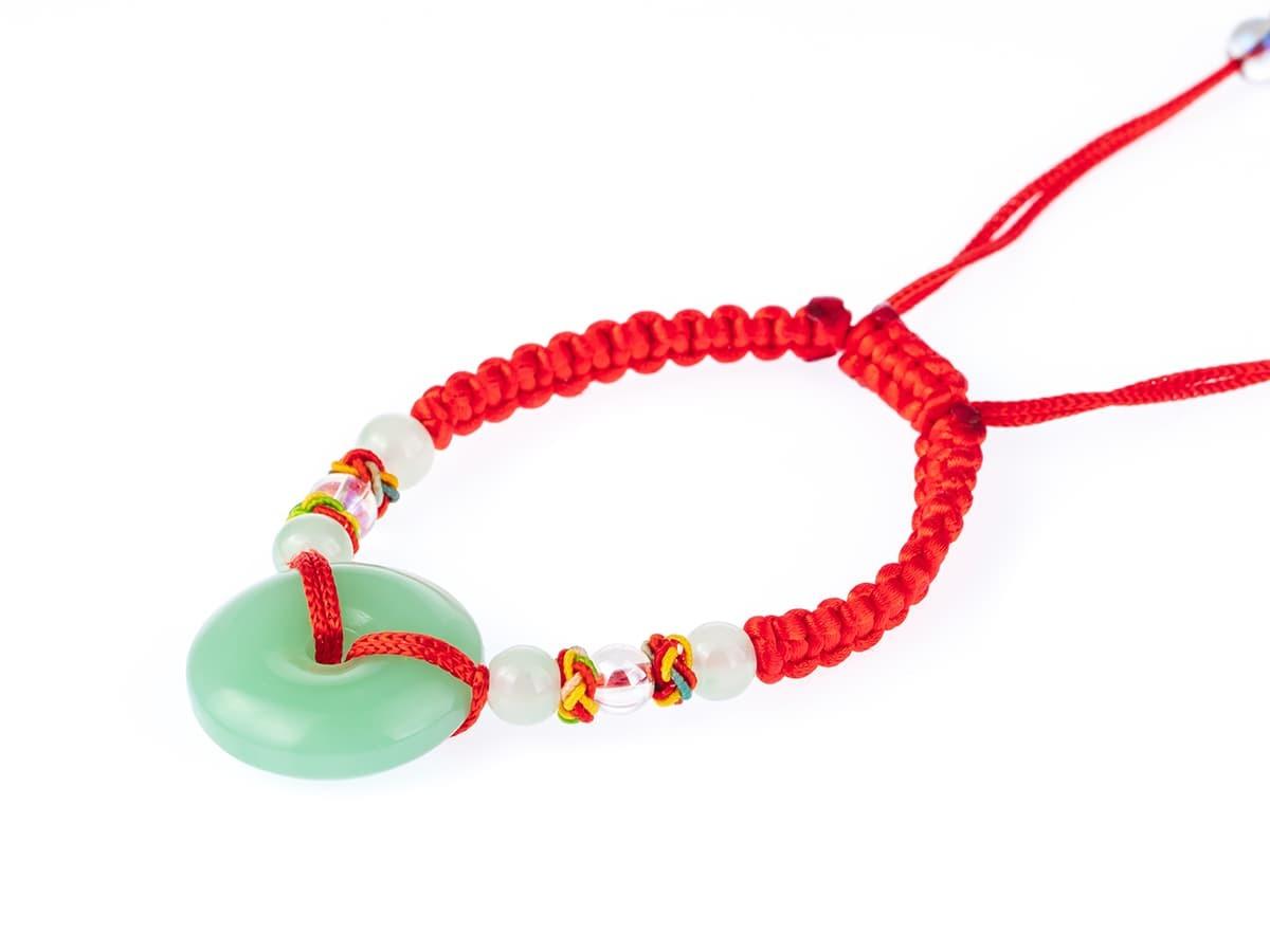 特別造型的玉石轉運珠,藉由左右兩條紅繩,固定玉石。